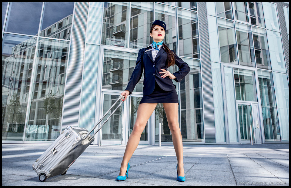 Commercial photography London. Sexy stewardess, flight attendant with a silver suitcase. Photo by Jarek Duk
