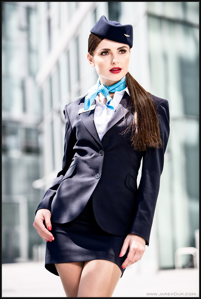 Commercial photography London. Sexy stewardess, flight attendant with a silver suitcase.
