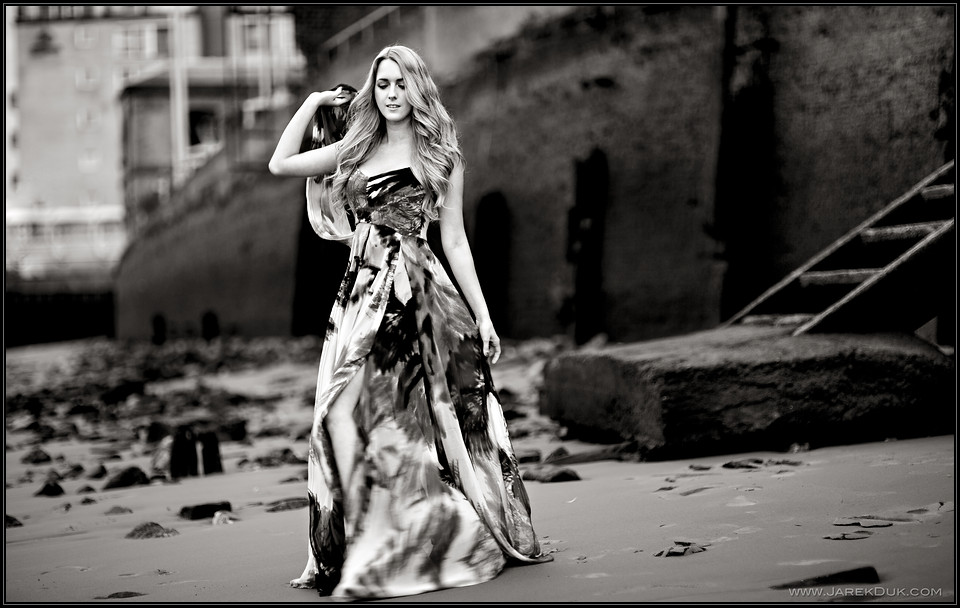 Fashion photography London. Romantic pattern dress on moody, nostalgic beach location.