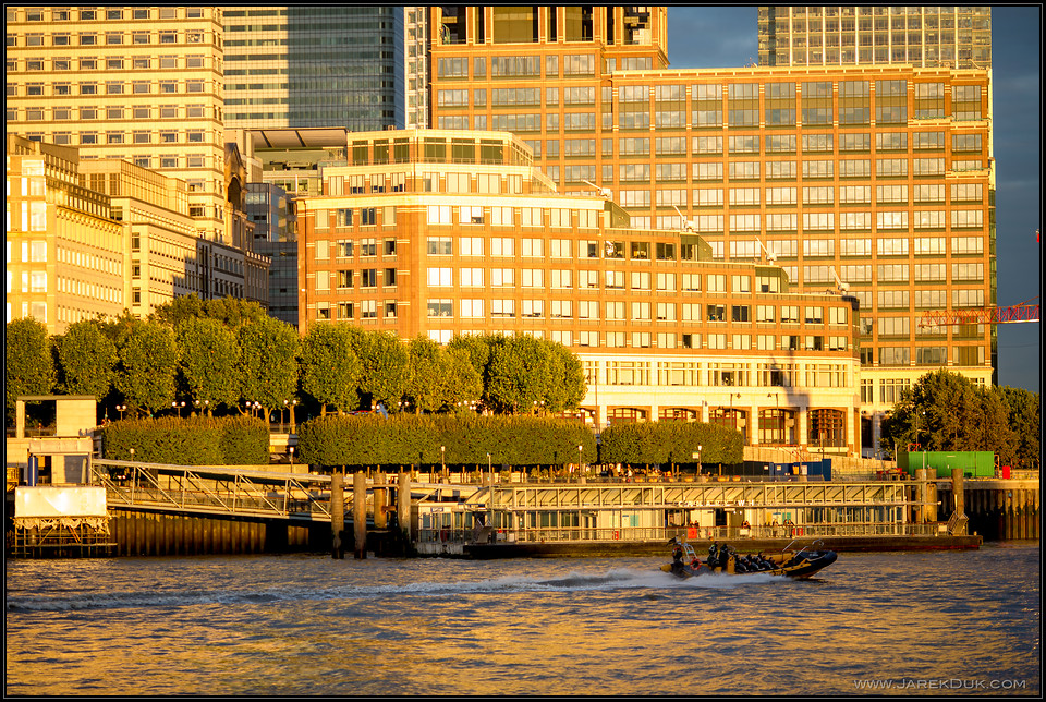 London sunset reflection on Canary Wharf buildings.