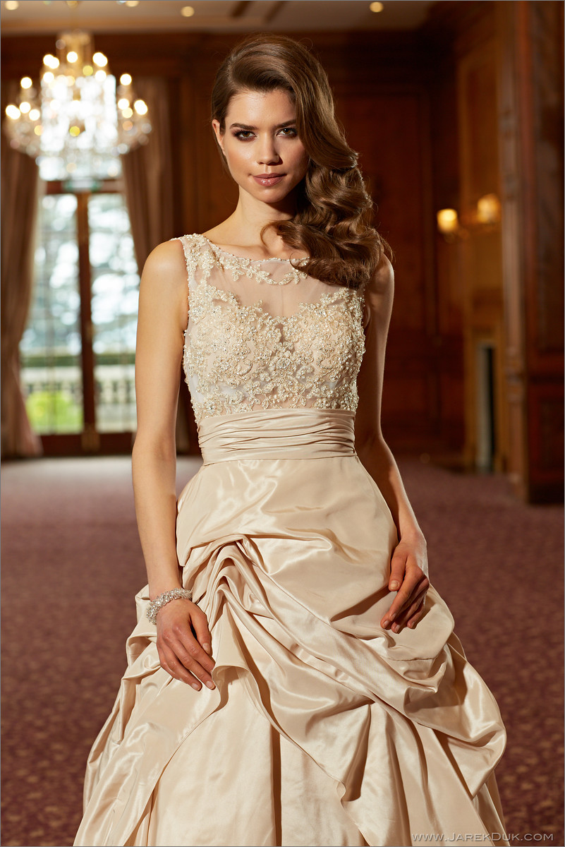 Bridal fashion photographer London. Beautiful bride in a beige, romantic wedding dress in a ballroom.